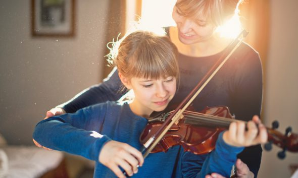 Little girl aged 9 is practicing violin. Mother is helping her by correcting her posture. Both are having fun during the lesson. The morning sun is backlighting them through the window.
