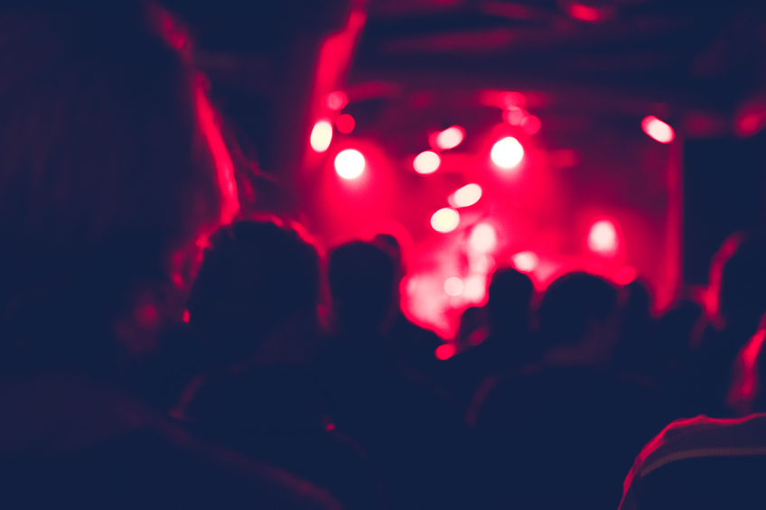 Defocused shot of people cheering on a rock concert. Group of unrecognisable people. Shot from back. The scene is illuminated with red lights.