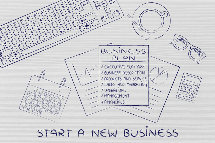 Business plan with sections on office desk, with text Start a new business